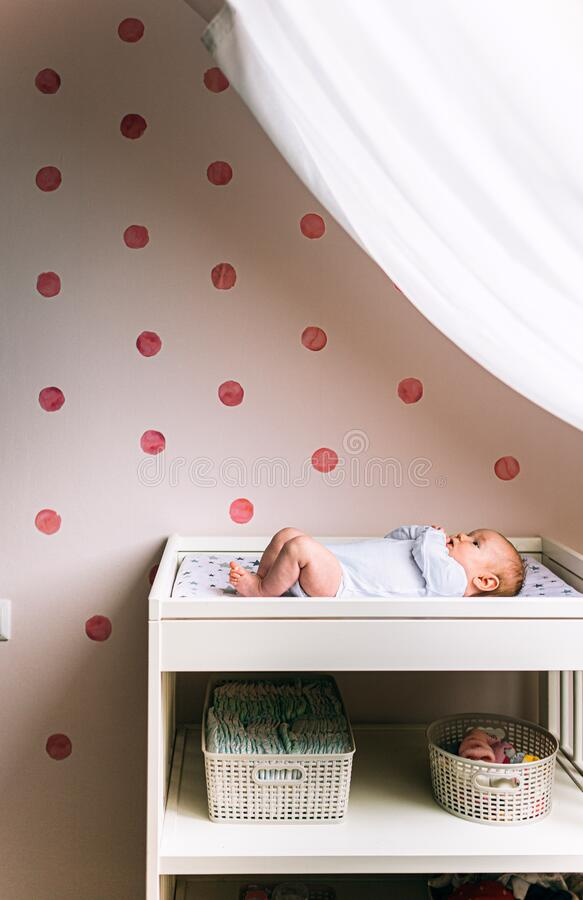 Little infant is lying on the kids table near window. There is Newborn child on the baby changing table. Vertical photo.  royalty free stock image