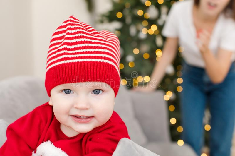 Little infant in striped hat looking at camera royalty free stock image