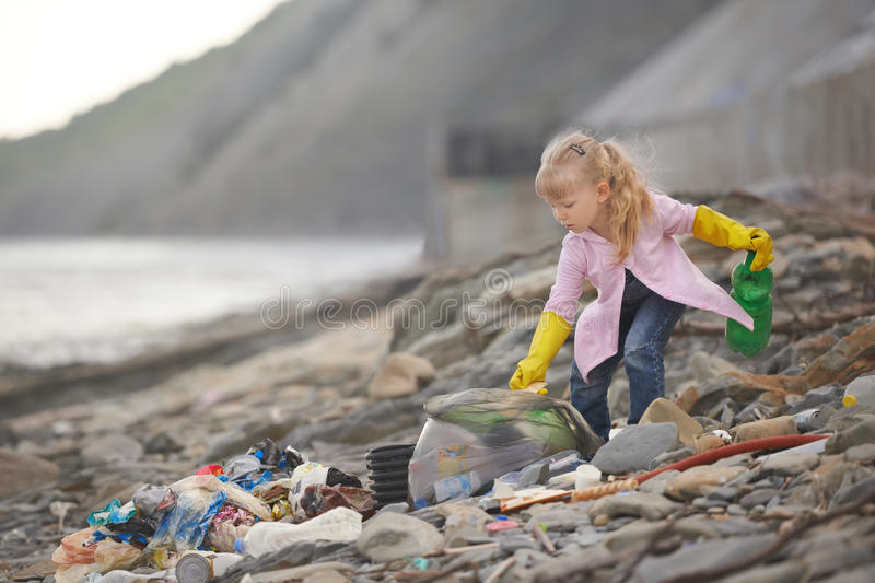 Little janitor picking up garbage at the beach royalty free stock photography
