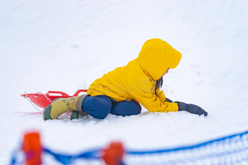 Little Japanese girl sliding down the snow sled in Gala Yuzawa Ski resort royalty free stock photos