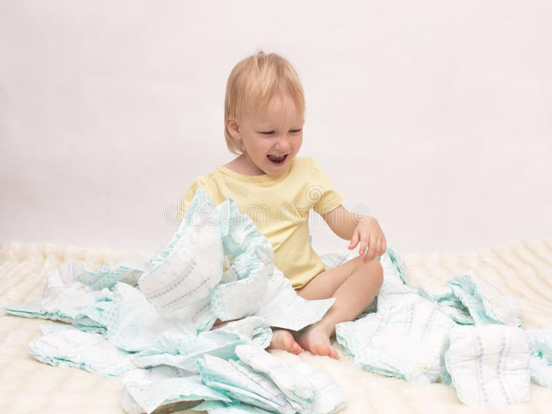 Little joyful girl playing with a pile of diapers on a white background, copy space, napkin stock photos