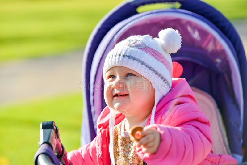 A little joyful girl in a red jacket and white cap rides in a baby carriage in the autumn park royalty free stock image