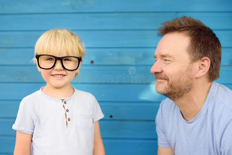 Little kid with big glasses and his father on blue wooden backgraund. Clever childs royalty free stock photo