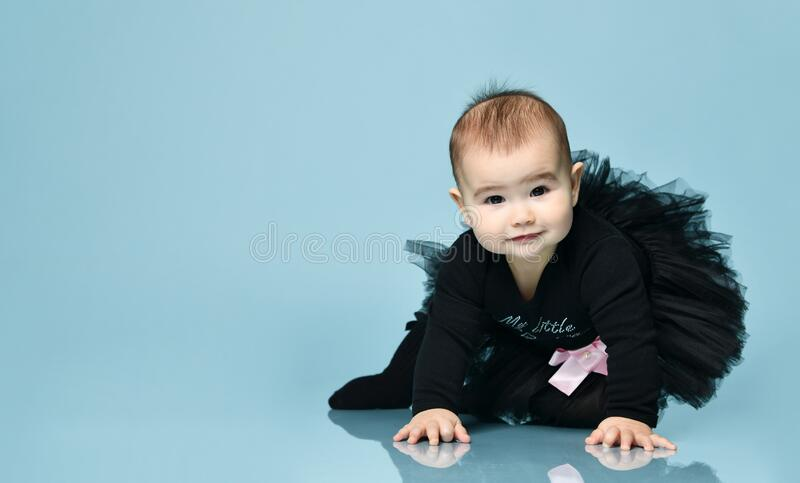 Little kid in black bodysuit with pink bow, poofy skirt and socks. She smiling, sitting on blue background. Close up, copy space. Little kid in black bodysuit royalty free stock photography