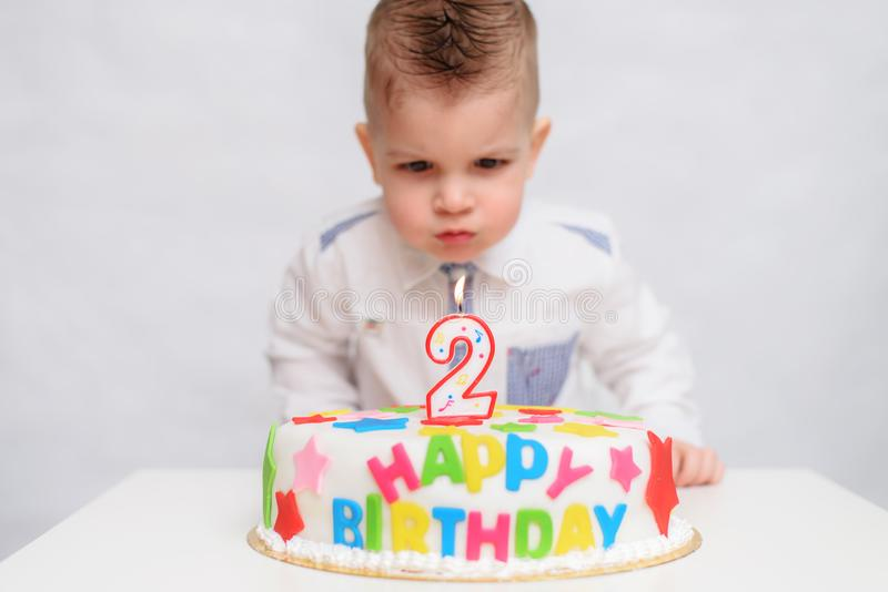 Little kid blows a candle on the cake on his birthday royalty free stock image