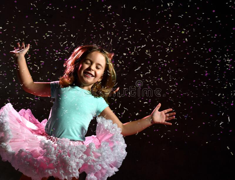 Little kid in blue t-shirt and poofy skirt. Smiling, closed eyes, jumping up against black background, pink backlight. Close up. Little kid in blue t-shirt and royalty free stock image