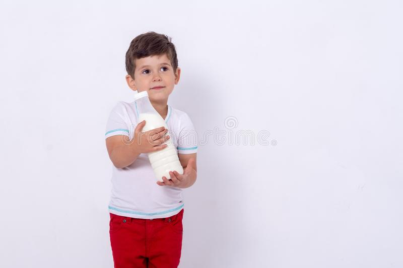 Little kid with bottle milk isolated background. Four years boy holding milk from from the farm. Dairy product for kids royalty free stock photography