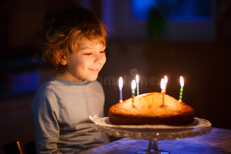 Little kid boy blowing candles on birthday cake. Adorable five year old kid boy celebrating his birthday and blowing candles on homemade baked cake, indoor royalty free stock images
