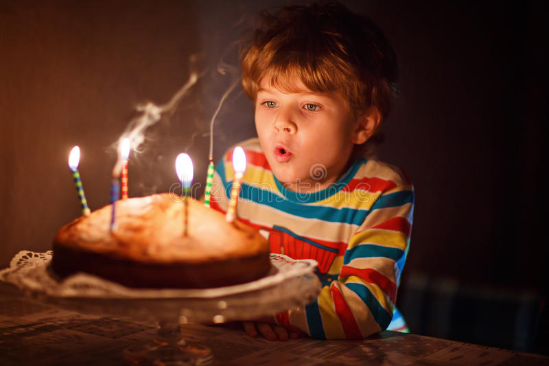 Little kid boy celebrating his birthday and blowing candles on cake. Happy little kid boy celebrating his birthday and blowing candles on homemade baked cake royalty free stock photo