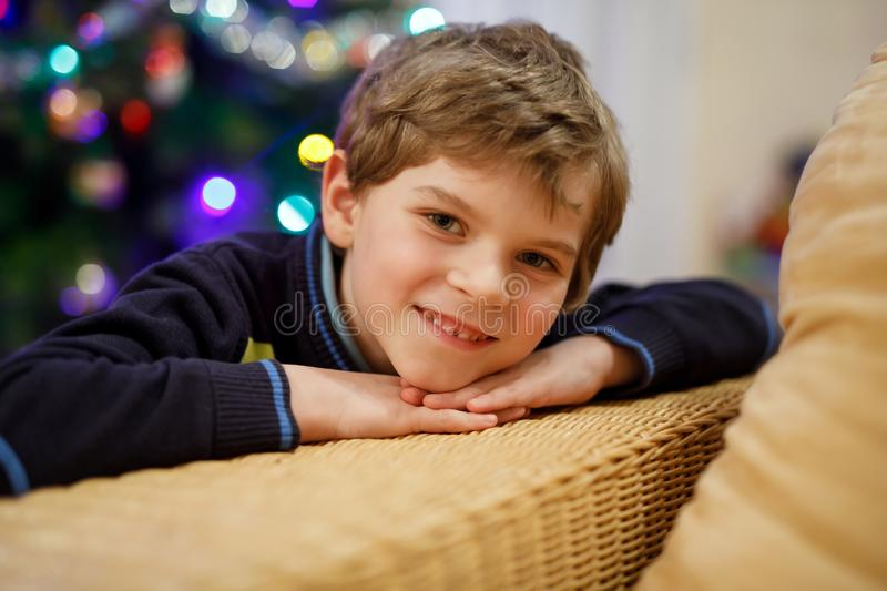 Little kid boy on Christmas Eve with Christmas tree and lights on background. With colorful illumination and garland. Happy preschool child celebrating xmas royalty free stock images