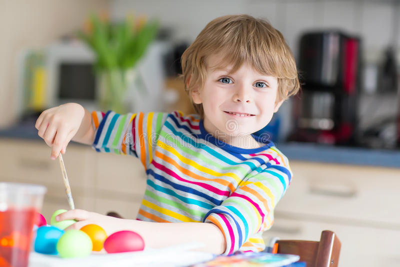Little kid boy coloring eggs for Easter holiday. Little blond kid boy coloring eggs for Easter holiday in domestic kitchen, indoors. Child having fun and royalty free stock photo