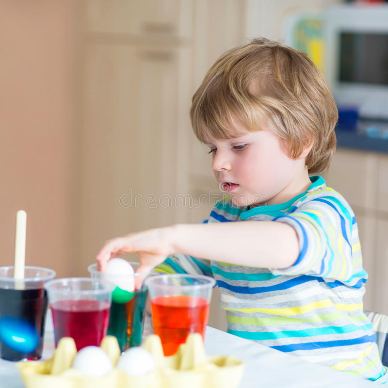 Little kid boy coloring eggs for Easter holiday. Cute toddler boy coloring eggs for Easter holiday in domestic kitchen, indoors. Child having fun and celebrating stock images
