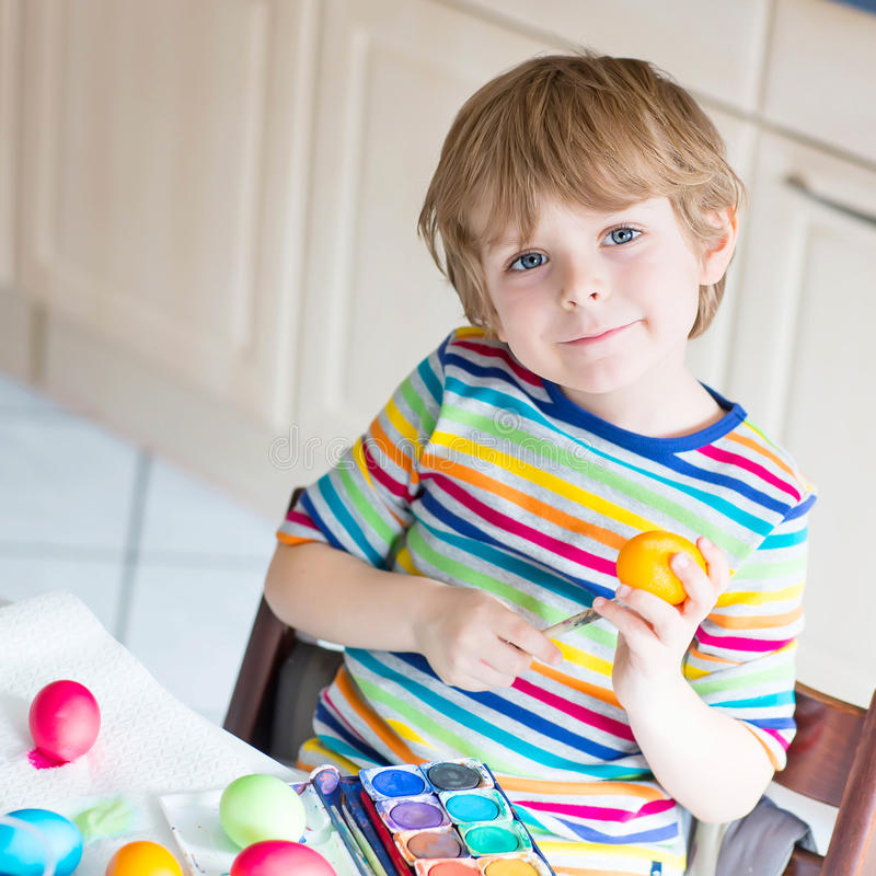 Little kid boy coloring eggs for Easter holiday. Happy little blond kid boy coloring eggs for Easter holiday in domestic kitchen, indoors. Child having fun and stock images