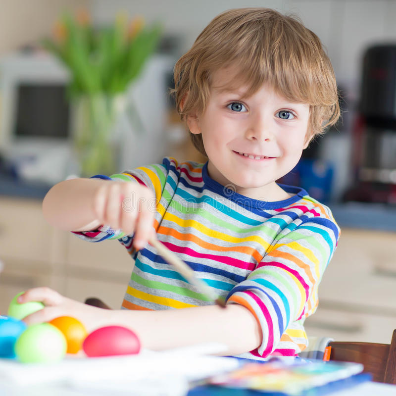 Little kid boy coloring eggs for Easter holiday. Happy kid boy of 4 years coloring eggs for Easter holiday in domestic kitchen, indoors. Child having fun and stock images
