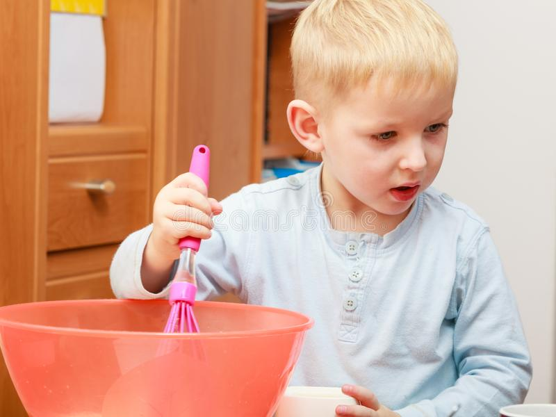 Little kid boy cooking, making cake in bowl stock photography