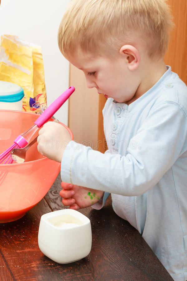 Little kid boy cooking, making cake in bowl royalty free stock photos