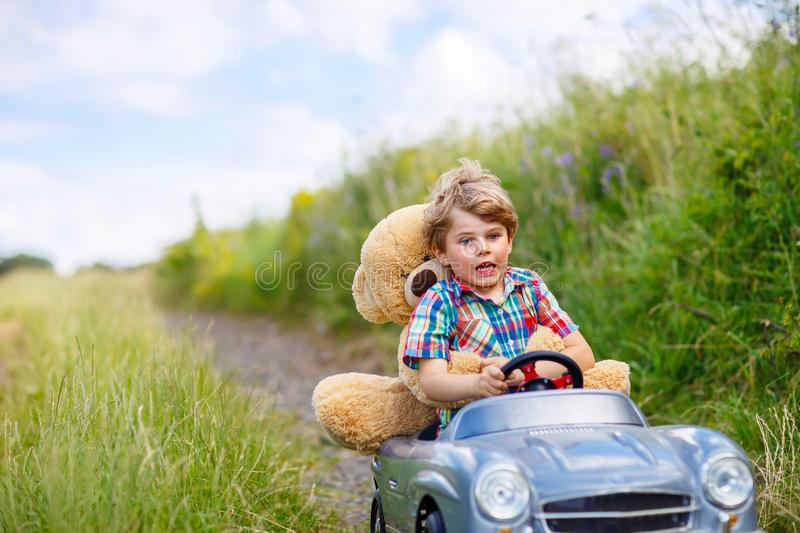 Little kid boy driving big toy car with a bear, outdoors. royalty free stock image