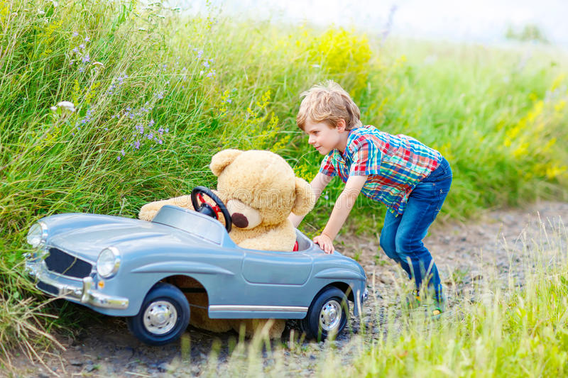 Little kid boy driving big toy car with a bear, outdoors. Little preschool kid boy driving big toy car and having fun with playing with his plush toy bear stock photos
