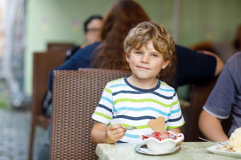 Little kid boy eating ice cream in outdoor cafe or restaurant. royalty free stock photo