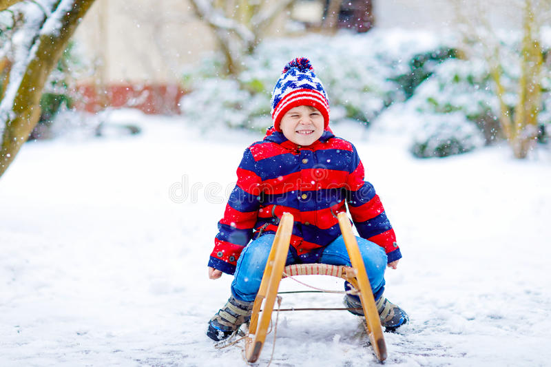Little kid boy enjoying sleigh ride in winter. Little boy enjoying sleigh ride. Child sledding. Toddler kid riding a sledge. Children play outdoors. Kids sled in royalty free stock photography