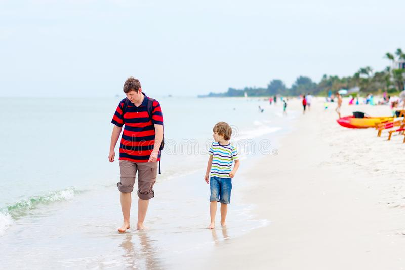 Little kid boy and father having fun with collecting shells stock image