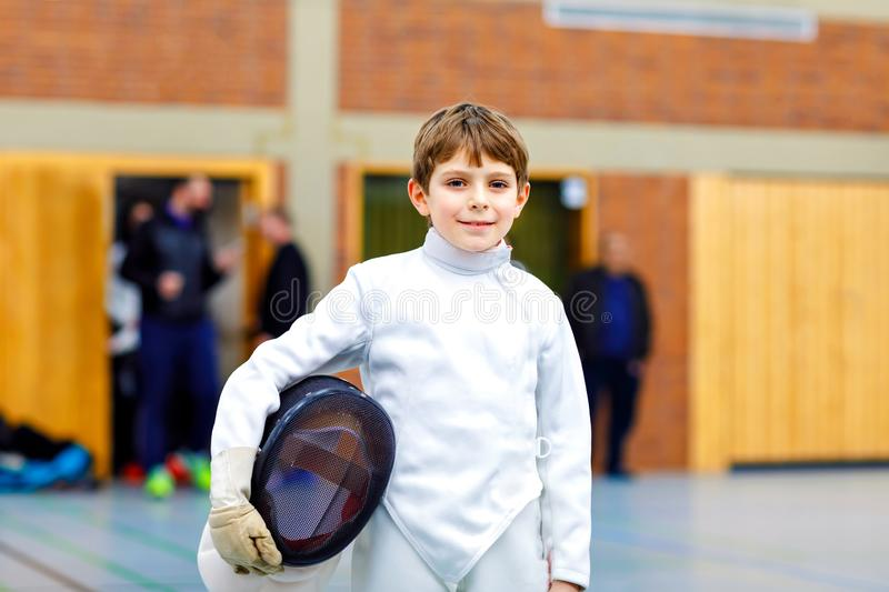 Little kid boy fencing on a fence competition. Child in white fencer uniform with mask and sabre. Active kid training stock photo