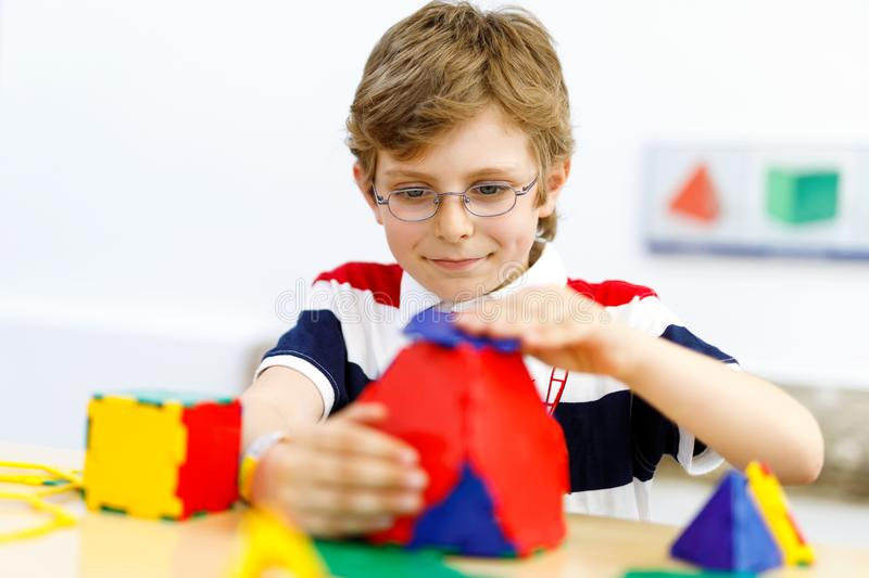 Happy kid boy with glasses having fun with building and creating geometric figures, learning mathematics and geometry. Little kid boy with glasses playing with stock photography