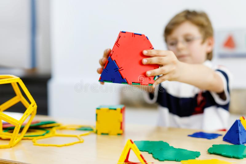 Little kid boy with glasses playing with lolorful plastic elements kit in school or preschool nursery. Happy child royalty free stock photo