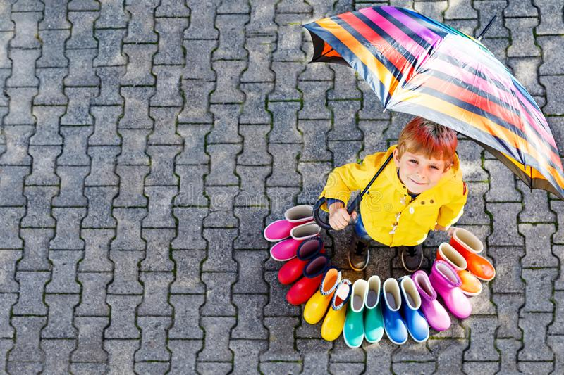 Little kid boy and group of colorful rain boots. Blond child standing under umbrella. Close-up of schoolkid and stock photo