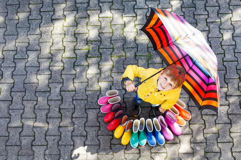 Little kid boy and group of colorful rain boots. Blond child standing under umbrella. royalty free stock photography
