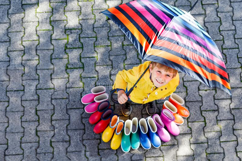 Little kid boy and group of colorful rain boots. Blond child standing under umbrella. Close-up of schoolkid and different rubber boots from high angle stock image