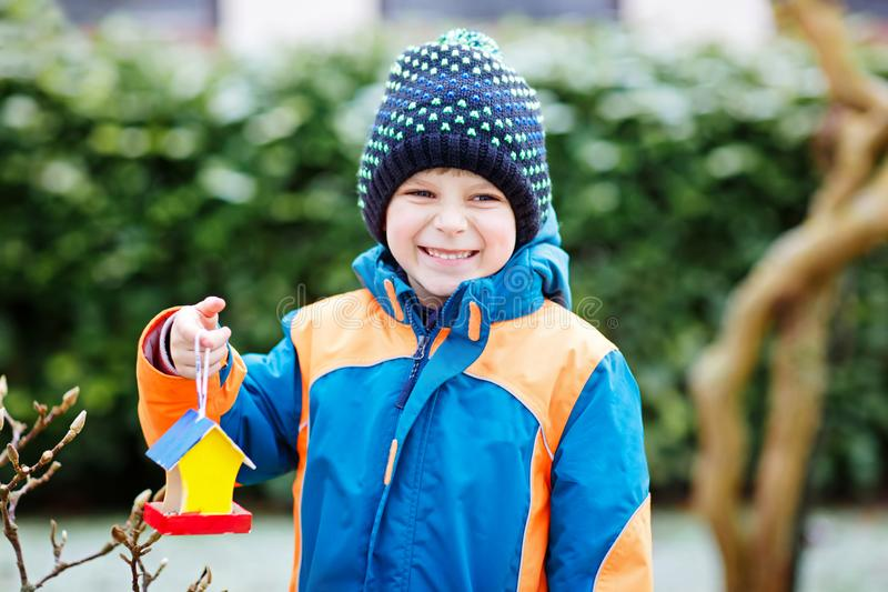 Little kid boy hanging bird house on tree for feeding in winter. Little kid boy feeding birds in winter. Cute happy preschool child hanging colorful selfmade royalty free stock images