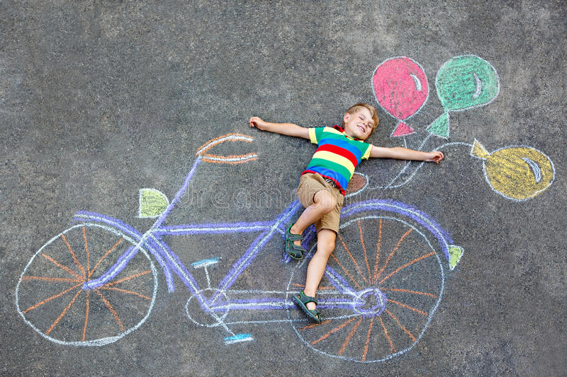 Little kid boy having fun with bike chalks picture stock photography
