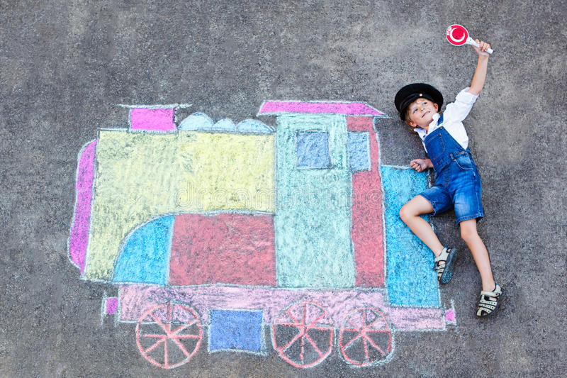 Little kid boy having fun with train chalks picture royalty free stock photography