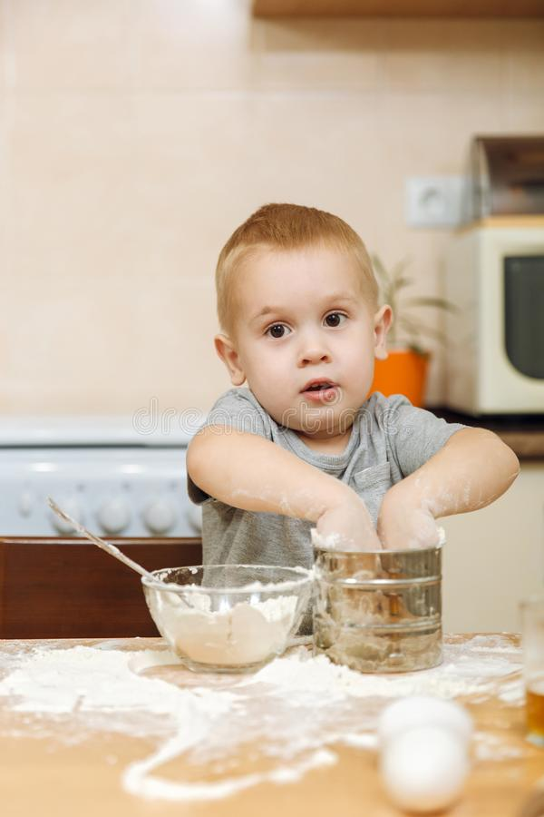 Little kid boy helps mother to cook ginger biscuit. Happy family mom and child in weekend morning at home. Relationship. royalty free stock photography