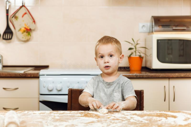 Little kid boy helps mother to cook ginger biscuit. Happy family mom and child in weekend morning at home. Relationship. A little kid boy helps mother to cook stock photography