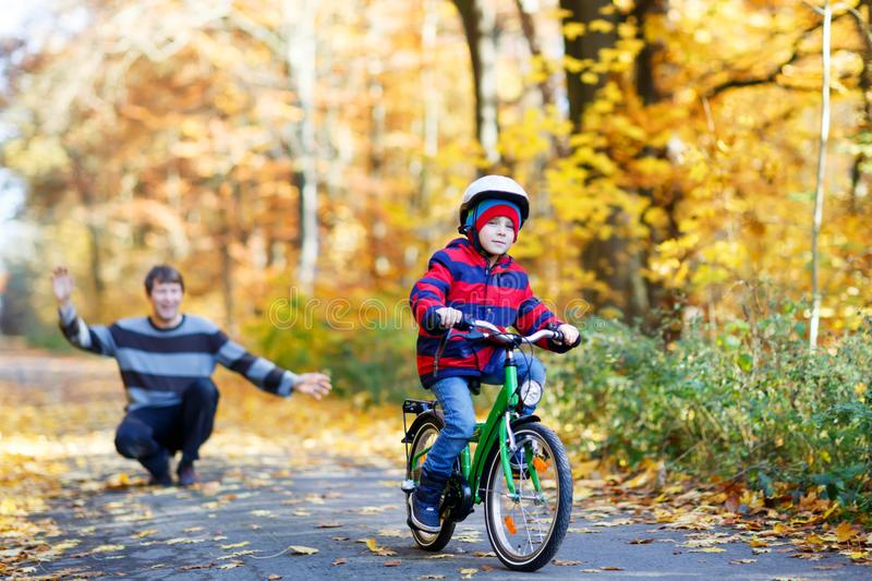 Little kid boy and his father in autumn park with a bicycle. Dad teaching his son biking. Active family leisure. Child with helmet on bike. Safety, sports royalty free stock image