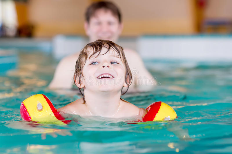 Little kid boy and his father swimming in an indoor pool stock photography