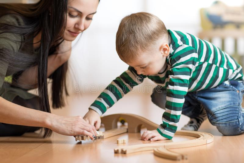 Little kid and his mother playing with railway sitting on the floor. stock images