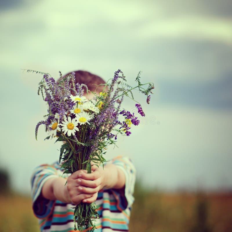 Little kid boy holding bouquet of fields flowers. Child giving flowers. Little kid boy in meadow bouquet of flowers at the countryside. Child giving flowers stock image