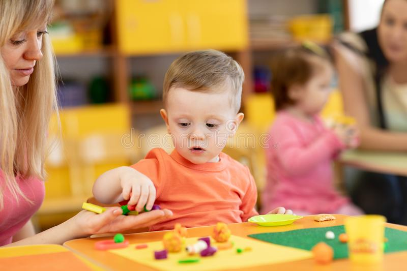 Little kid boy learning to use colorful play clay in kindergarten. Babies group studying in creche royalty free stock images