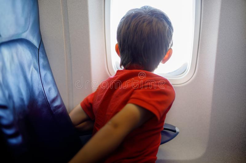 Little kid boy looking outside of plane window during flight on airplane. royalty free stock photography
