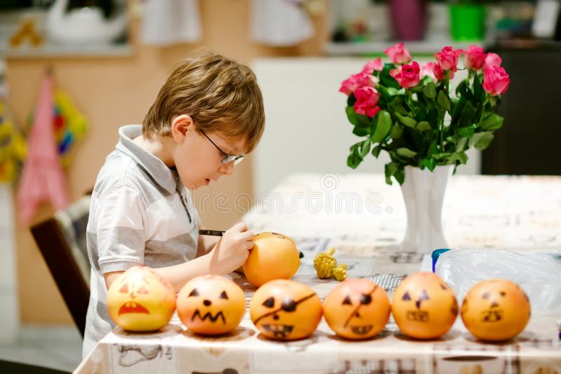 Little kid boy making Jack-o-lantern with drawing scary faces on mandarine, tangerine or clementine. Happy child making royalty free stock images