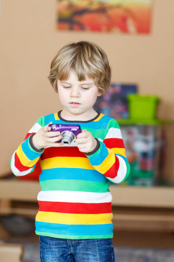 Little kid boy making photos with photocamera, indoors. Active kid boy making photos with photocamera, indoors. Child wearing colorful shirt. Portrait in a royalty free stock photography