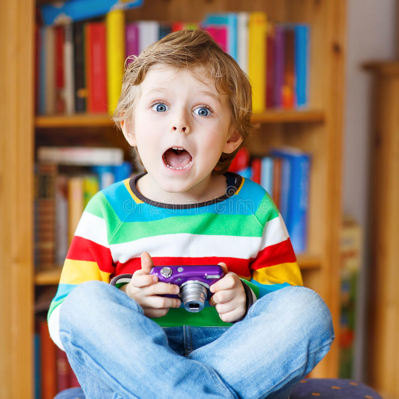 Little kid boy making photos with photocamera, indoors. Active kid boy having fun with making photos with photocamera, indoors. Child wearing colorful shirt stock images