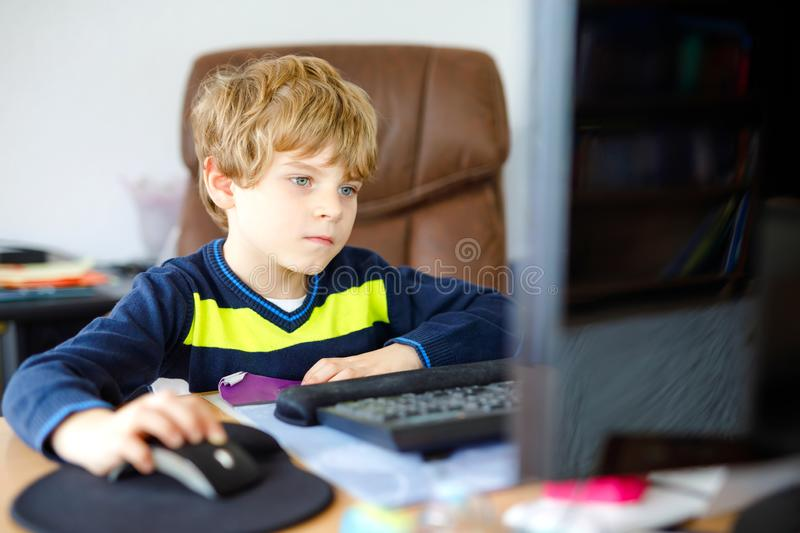 Little kid boy making school homework on computer notebook. Happy healthy child searching information on internet. New. Media education, kid watching learning stock images