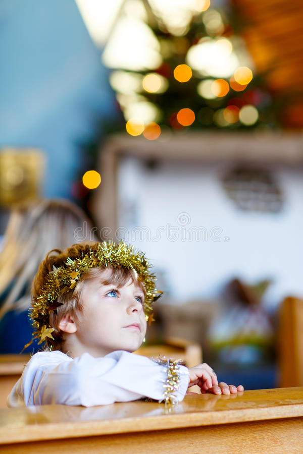 Little kid boy playing an angel of Christmas story in church stock photo