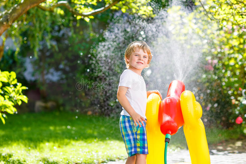 Little kid boy playing with a garden hose. Happy little kid boy playing with a garden hose on hot and sunny summer day. Child having fun outdoors. Funny outdoors royalty free stock photo