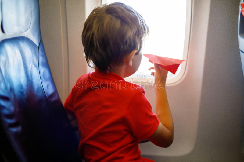 Little kid boy playing with red paper plane during flight on airplane. Child sitting inside aircraft by a window. Family going on vacation royalty free stock photography