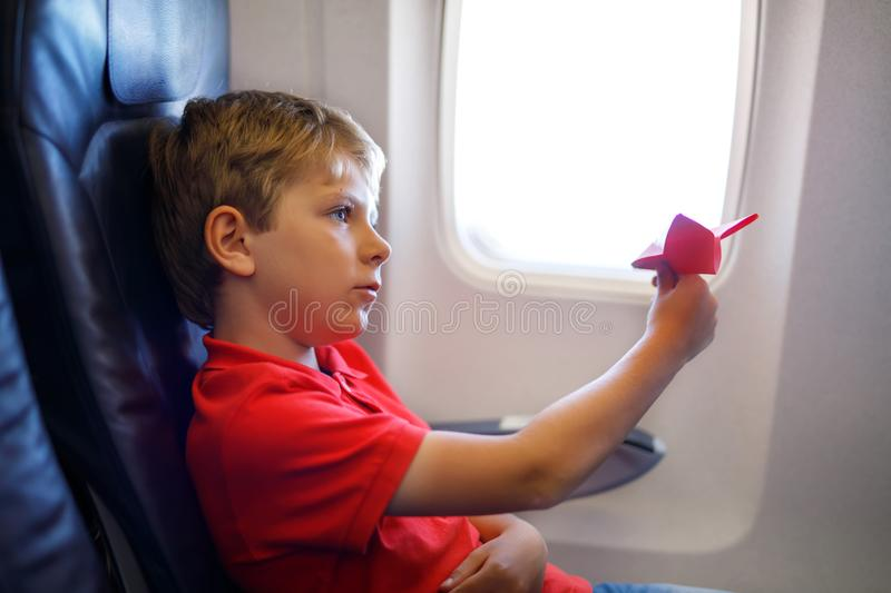Little kid boy playing with red paper plane during flight on airplane. Child sitting inside aircraft by a window. Family. Going on vacation stock image